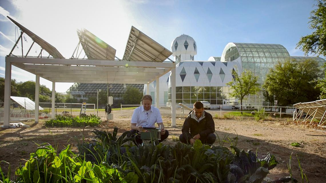 Agrivoltaics at Biosphere 2 with Greg Barron-Gafford and assistant under panels growing food.